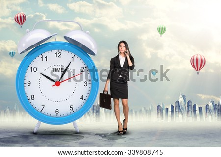 Lady talking on cell phone with big alarm clock on city background - stock photo