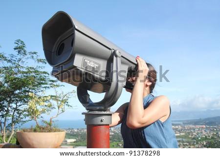Lady tourist looking through a telescope. - stock photo