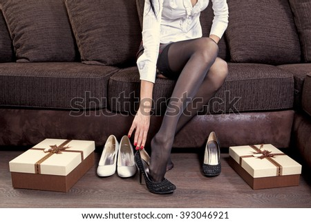 lady trying on several pairs of new shoes in the mall - stock photo