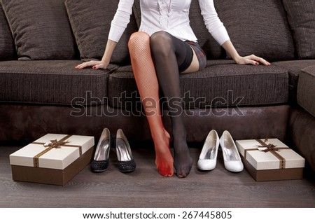 lady trying on several pairs of shoes in the mall - stock photo