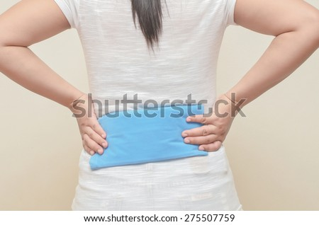 Lady use cold-hot pack to relieve back pain. - stock photo