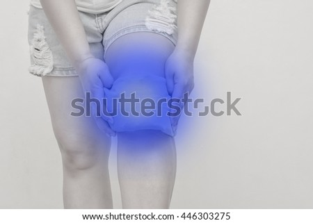 Lady Use cold-hot pack to relieve knee pain.Concept photo with Color Enhanced pale skin with blue spot indicating location of the pain and cold.