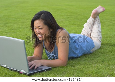 lady using laptop in field side view - stock photo