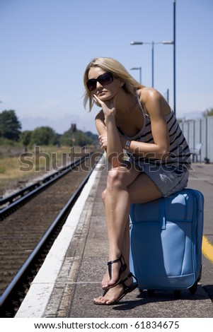 Lady waiting for a train sitting on her luggage - stock photo
