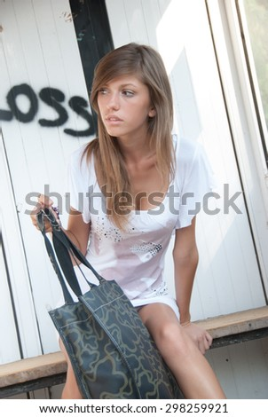 Lady waiting on cheap bus stop , she is wearing a short white dress, she have the bag between her legs - stock photo