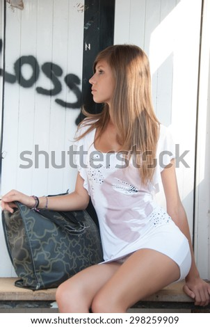 Lady waiting on cheap bus stop , she is wearing a short white dress, she have the bag side to her legs - stock photo