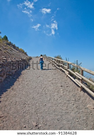 Lady walking for exercises during a sunny day on a mountain path - stock photo