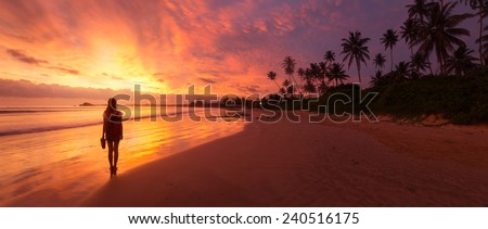 Lady walking on the wet sandy beach during sunset - stock photo