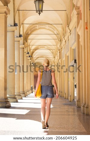 Lady walking the old traditional streets of Bologna, Italy. - stock photo