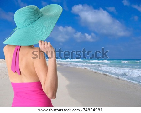Lady wearing a sun hat on a Caribbean beach - stock photo