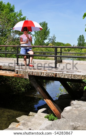 Lady with an umbrella on a bridge