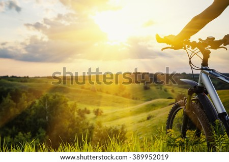 Lady with bicycle on a rural road with grass enjoying sunset - stock photo