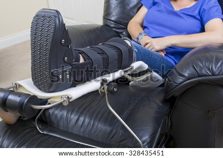 Lady with Fractured Leg  A lady with a fractured leg sat in an armchair with her injured leg in an orthopeadic boot supported on a raised leg support - stock photo