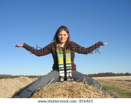 Lady with outstretched arms on hay roll. - stock photo