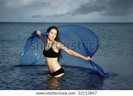 Lady with perfect body dancing in the sea with blue fabric - stock photo