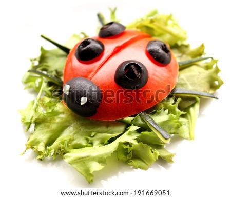 Ladybug made of raw tomato on lettuce leaf - stock photo