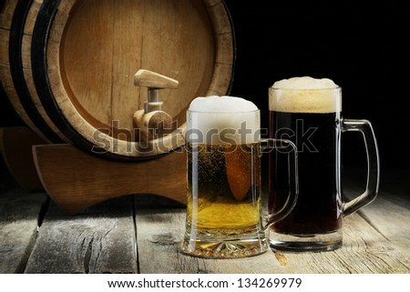 Lager and dark beer on the old wooden background with keg or barrel of beer. - stock photo