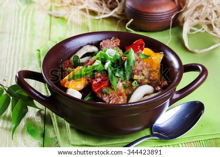 Lagman with meat in a clay pot on a wooden board still life green bright beautiful appetizing menu, delicious food - stock photo