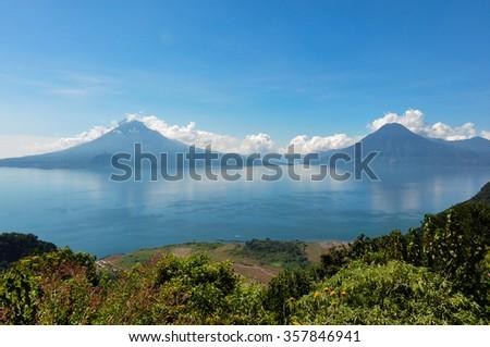 Lago Atitlan along with 2 volcanoes, Panajachel, Guatemala. - stock photo