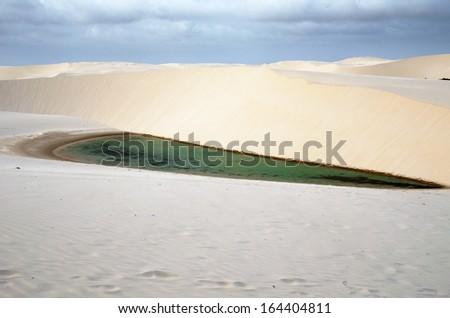 Lagoa azul in desert white sand dunes of the Lencois Maranheses National Park in brazil - stock photo