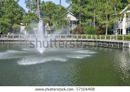 Lagoon and fountain by a resort building.  The resort is on Hilton Head Island in South Carolina. - stock photo