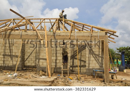 LAGOS, NIGERIA - JULY 25, 2012: Two african workers building a typical house, made of concrete blocks and wood strips, in the large city of Lagos, Nigeria, on July 25, 2012