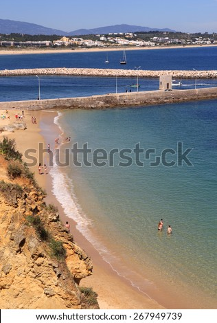 LAGOS, PORTUGAL - APRIL 01: Tourists sunbathing in the warm, spring sunshine on the town beach of Lagos in the Western Algarve. On April 01, 2015 in Lagos, Portugal. - stock photo