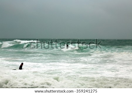 Laguna Beach CA: 1-6-2016, Surfers swim out to Surf the Higher than usual waves in Laguna Beach as the El Nino Storm of 2016 makes landfall and causes flooding and damage around southern California. - stock photo