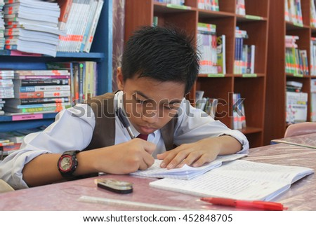 Lahad Datu, Sabah Malaysia- JULY 14, 2016: Malaysian lower secondary student spending time doing his school work in the school library