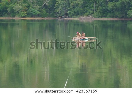 Lahad Datu Sabah Malaysia - May 8, 2016 : Villager using traditional boat or sampan to cross lake in Lahad Datu Sabah on May 8, 2016.