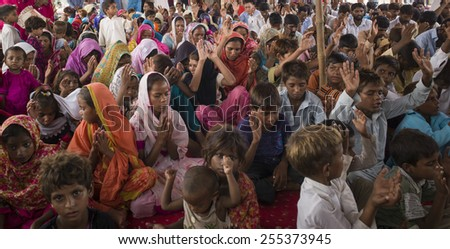 LAHORE, PAKISTAN- AUG 2: Unidentified children in brick kiln are praying and waiting for the food from relief team on August 2 2012 in Lahore, Pakistan.  - stock photo
