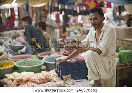 LAHORE, PAKISTAN- AUG 1 : Unidentified hawker in local market in the slum on August 1 2012 in Lahore, Pakistan. The slum is under poor hygiene condition and people suffer from serious health issues.  - stock photo