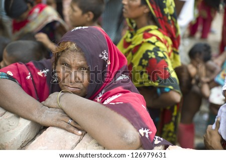 LAHORE, PAKISTAN- AUG 2: Unidentified woman in brick kiln is waiting for the food from relief team on August 2 2012 in Lahore, Pakistan. - stock photo