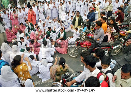 LAHORE, PAKISTAN - NOV 24: Angry protesters stop motorists to move forward during protest demonstration of Young Nurses Association (YNA) in favor of their demands on November 24, 2011in Lahore, Pakistan. - stock photo
