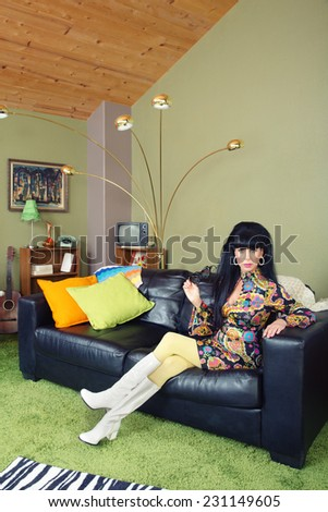Laid back pretty retro woman sitting on leather sofa - stock photo