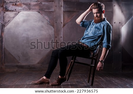 Laid-back style . Picture of a handsome young bearded man posing while sitting on chair