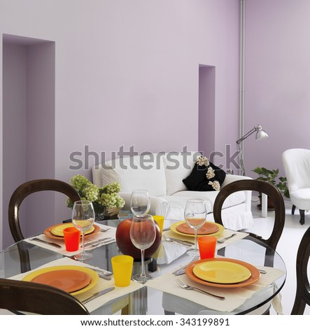 laid table in the living room with walls of lilac color - stock photo