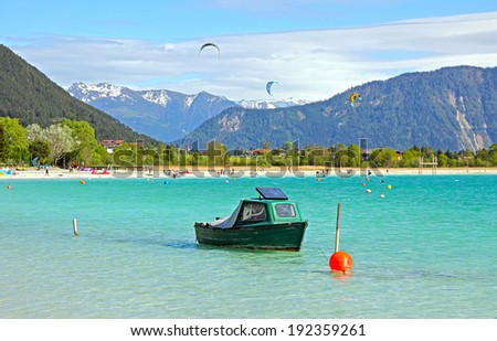 lake achensee with fishing boat and kite surfers, picturesque tourist resort - stock photo