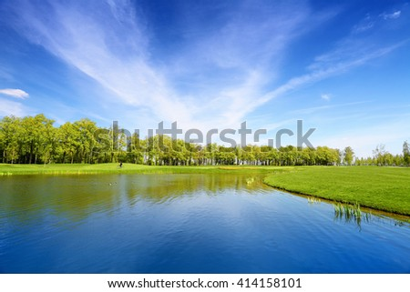 Lake and green meadow. Landscape in summer day. Blue sky reflected in water