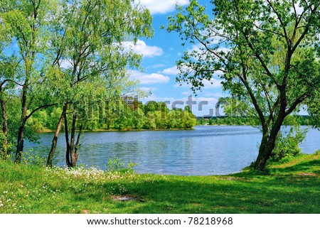 lake and green meadow near the water in sunny day - stock photo