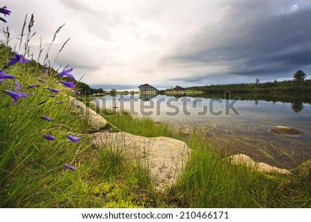 lake and hut on the rainy sky  - stock photo