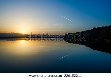 Lake and power lines at sunset with a yellow bright sun at the horizon woods with trees on the right and an airplane vapor trail on the blue sky reflecting on the water - stock photo