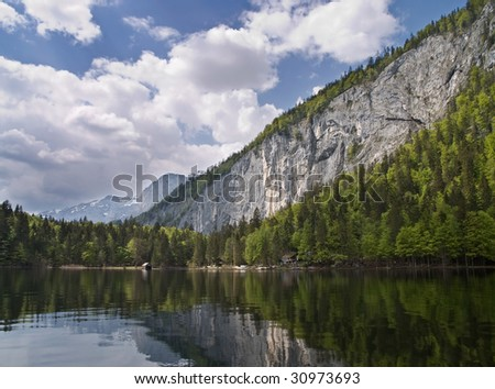 Lake and rocky mountain wall - stock photo
