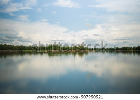 Lake and sky.view on the lake and forest at evening time just before the sunset. Sky and clouds reflected in water surface.