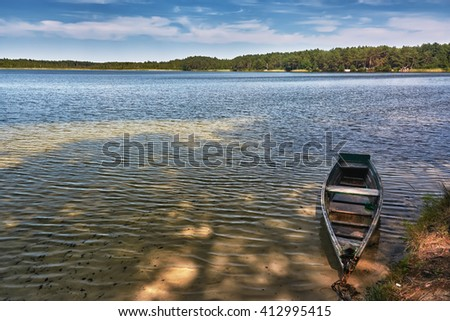 Lake and wooden fishing boat at the shore. - stock photo
