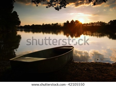 Lake at Sunset with Boat - stock photo