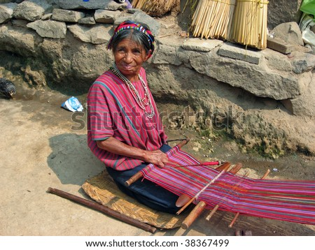 LAKE ATITLAN, GUATEMALA-MAY 15: Mayan woman performs traditional craft of weaving on a primitive loom May 15, 2009 in Lake Atitlan, Guatemala.