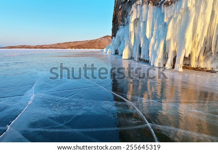 Lake Baikal. Reflection of icy rocks in a smooth ice surface in February evening - stock photo