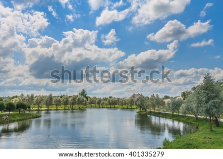 lake, blue sky, green grass and trees landscape on sunny spring or summer day
