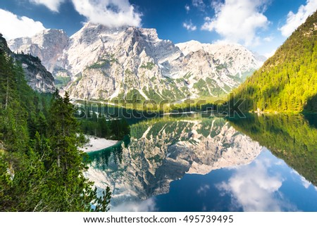 Lake Braies known as Lago di Braies. The lake is surrounded by the mountains reflected in the water.1st point of the trekking route Alta Via, The Dolomites, Alps, South Tyrol, Italy. Warm colors